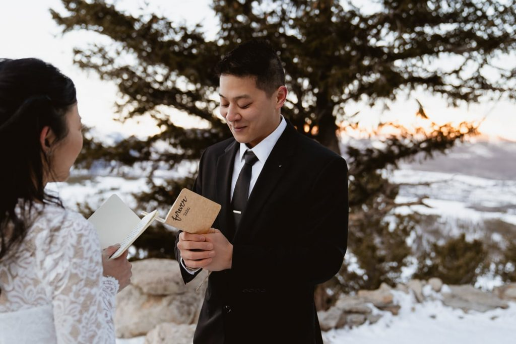 Groom smiles as her reads his wedding vows to his new future wife in the snow, the sunlight lighting up the mountain range behind him