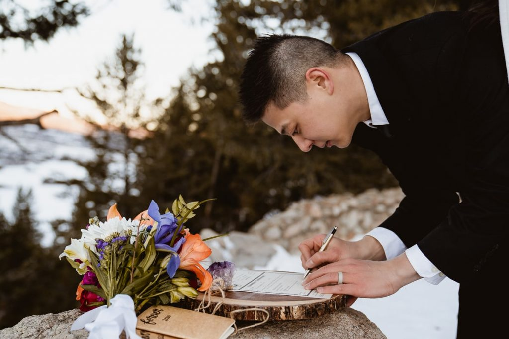 Groom signs the marriage license at his winter Sapphire Point elopement