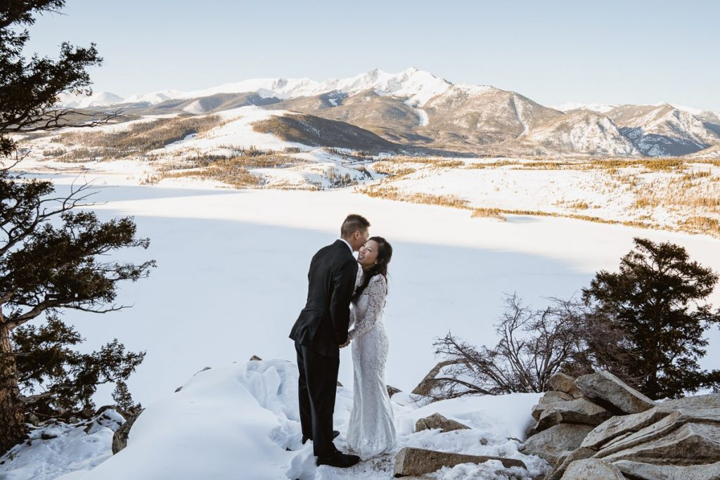 The groom whispers in the brides ear and she giggles as they pose in front of this vast landscape at Sapphire Point Overlook in Colorado