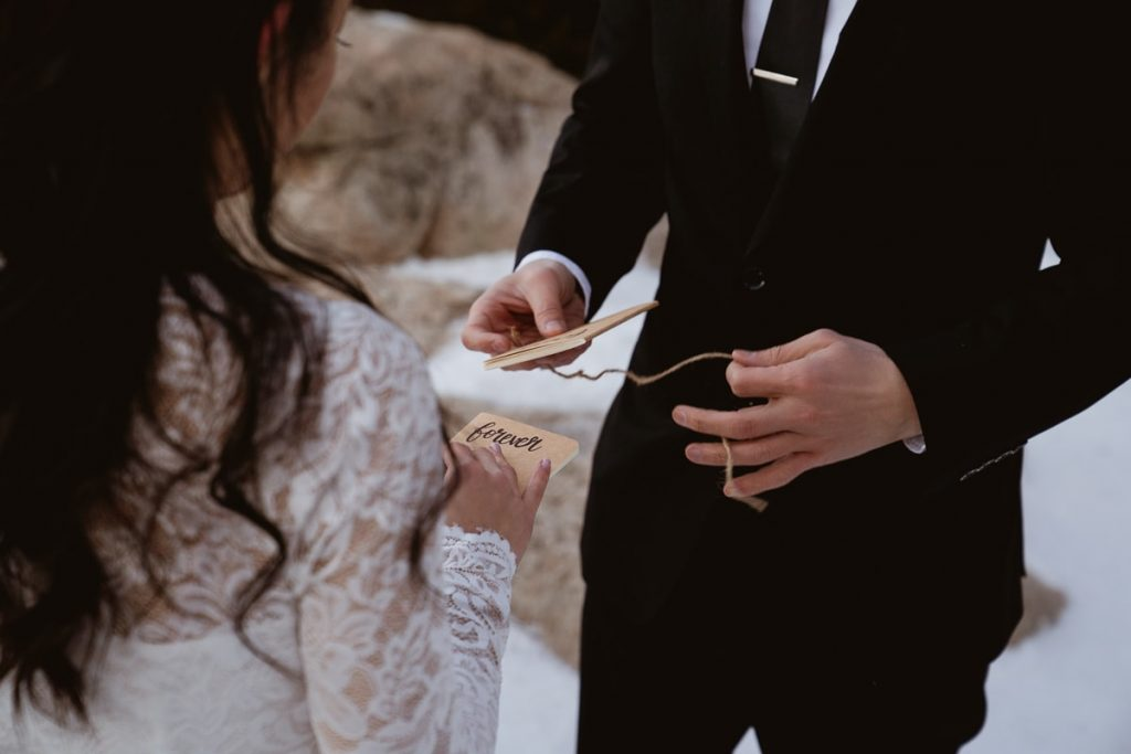 Bride and groom hold their handmade vow books before saying their vows during their winter Sapphire Point Elopement