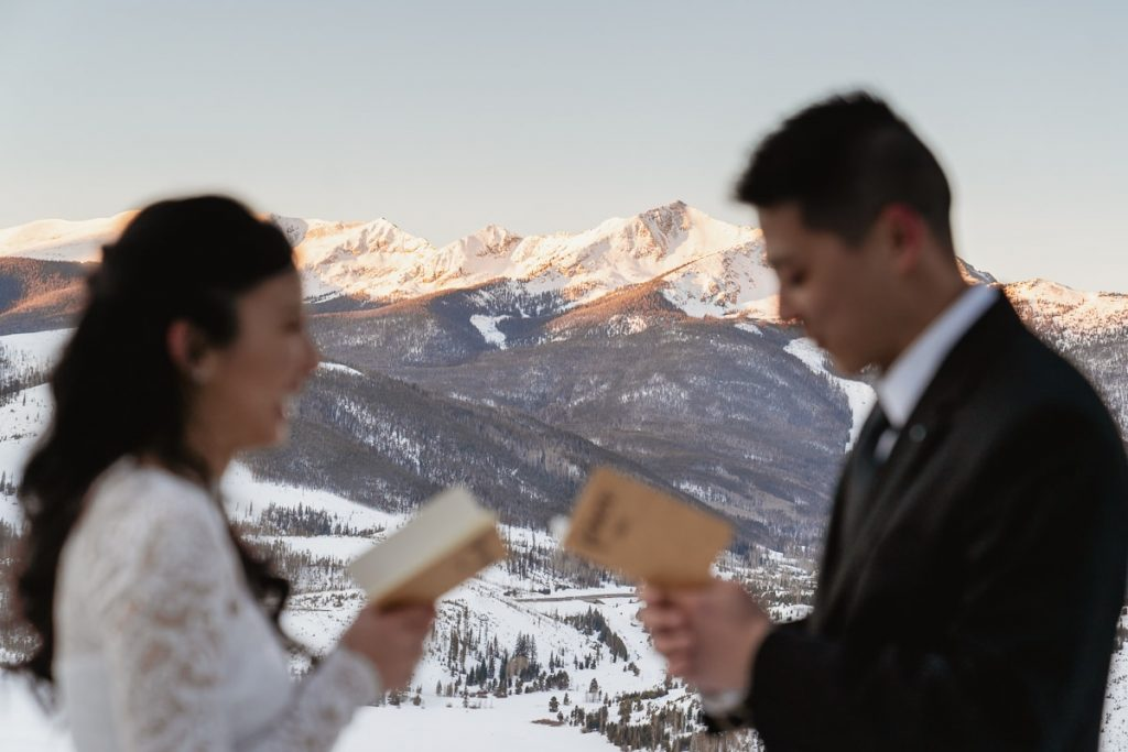 Detailed photo of the sunlight mountain range between the couple as they say their wedding vows at their spontaneous winter Sapphire Point elopement