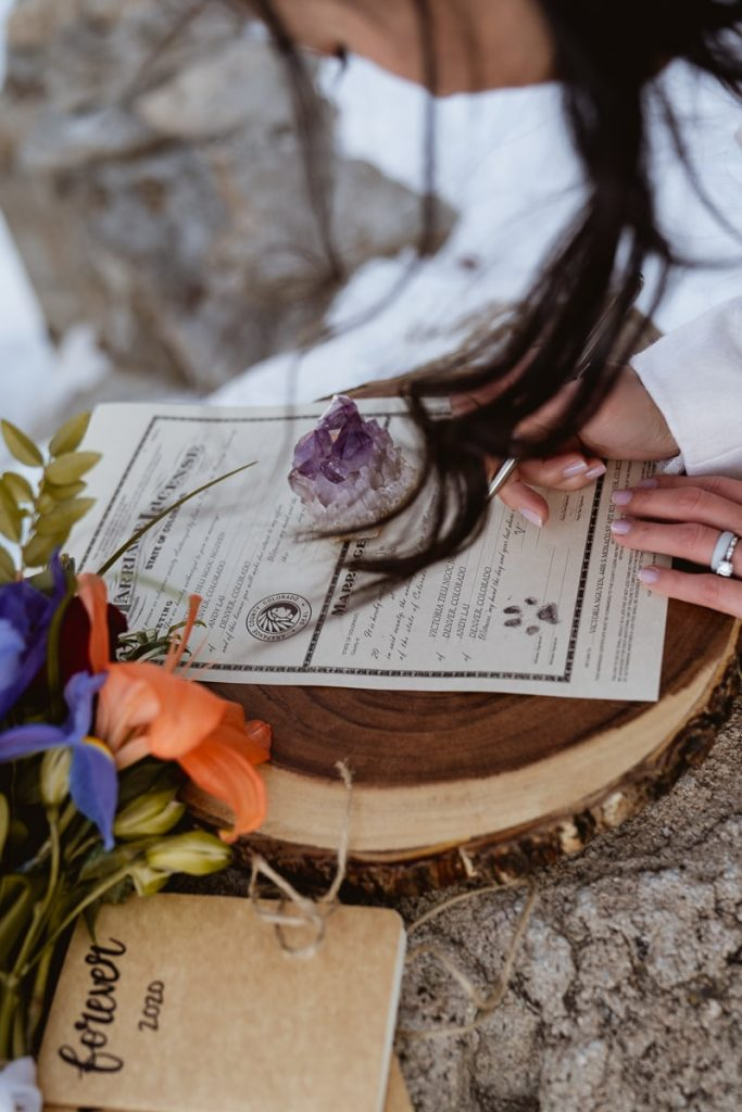 Bride finishes up marriage license with a closeup detail of the paw print on Colorado marriage license. Such a cute idea for their winter Sapphire Point elopement