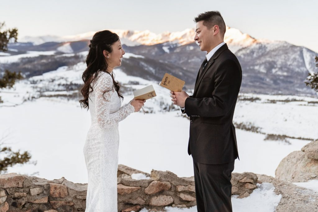 Bride and groom smile at each other during ceremony with snowy mountains behind them