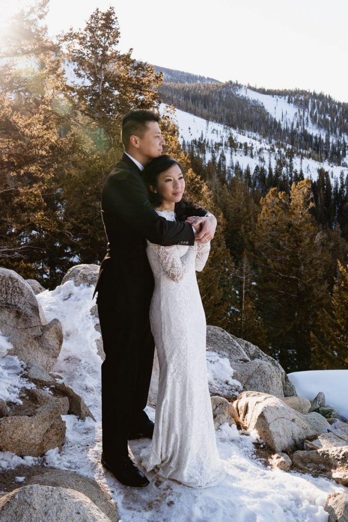 The sun starts to peak over the mountain as the bride and groom cuddle during this sunrise winter Sapphire Point elopement