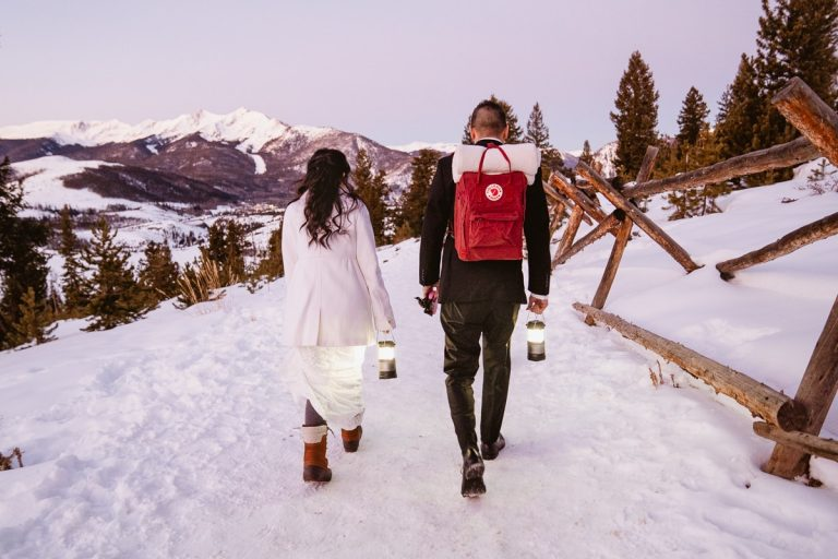 Bride and groom walk to ceremony location in the snow for this winter sapphire point elopement
