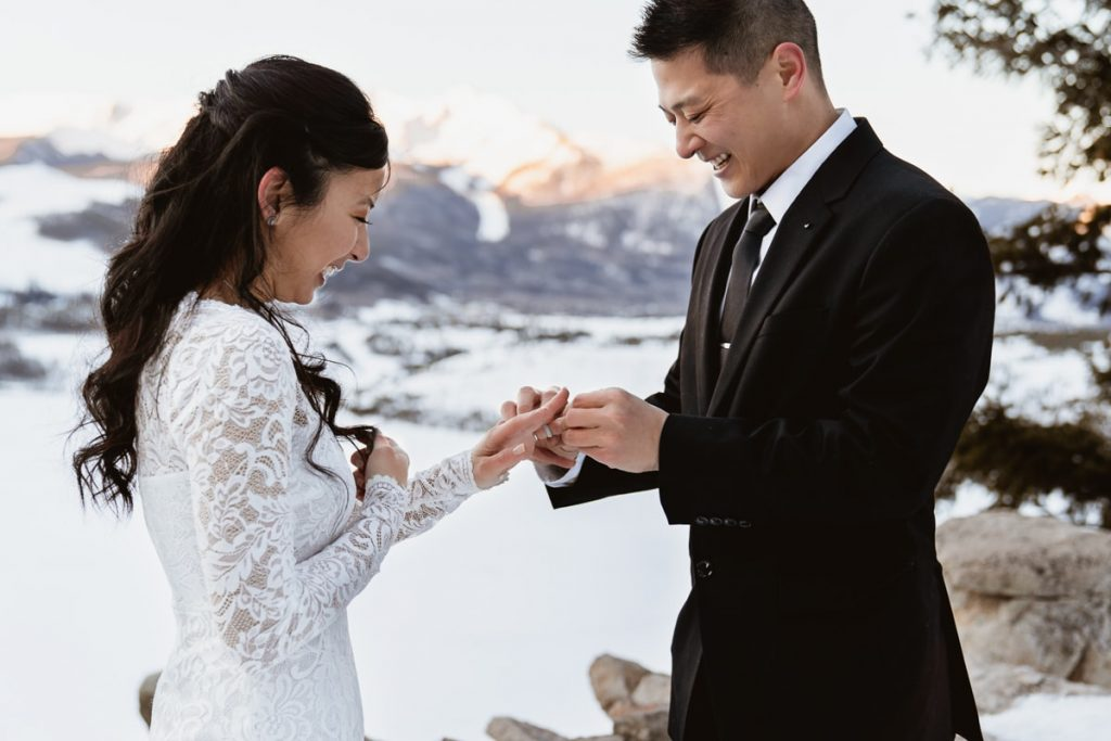 Having a winter Sapphire point elopement is the best way to get married. The groom had a little trouble putting on the wedding bands because their hands were so cold