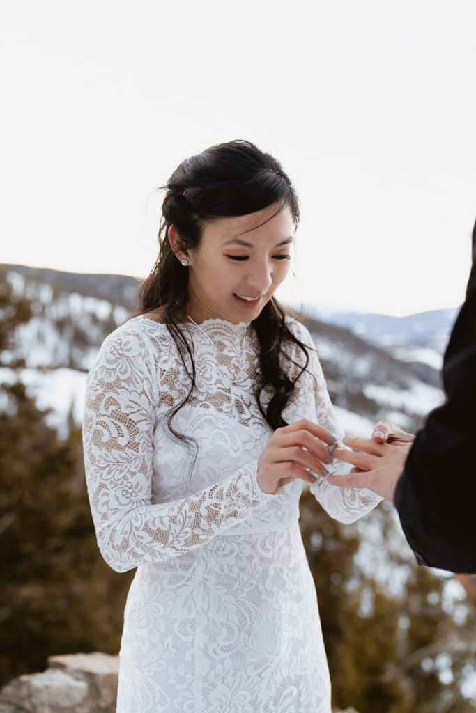 Bride puts on the groom's wedding band for this winter Sapphire Point elopement