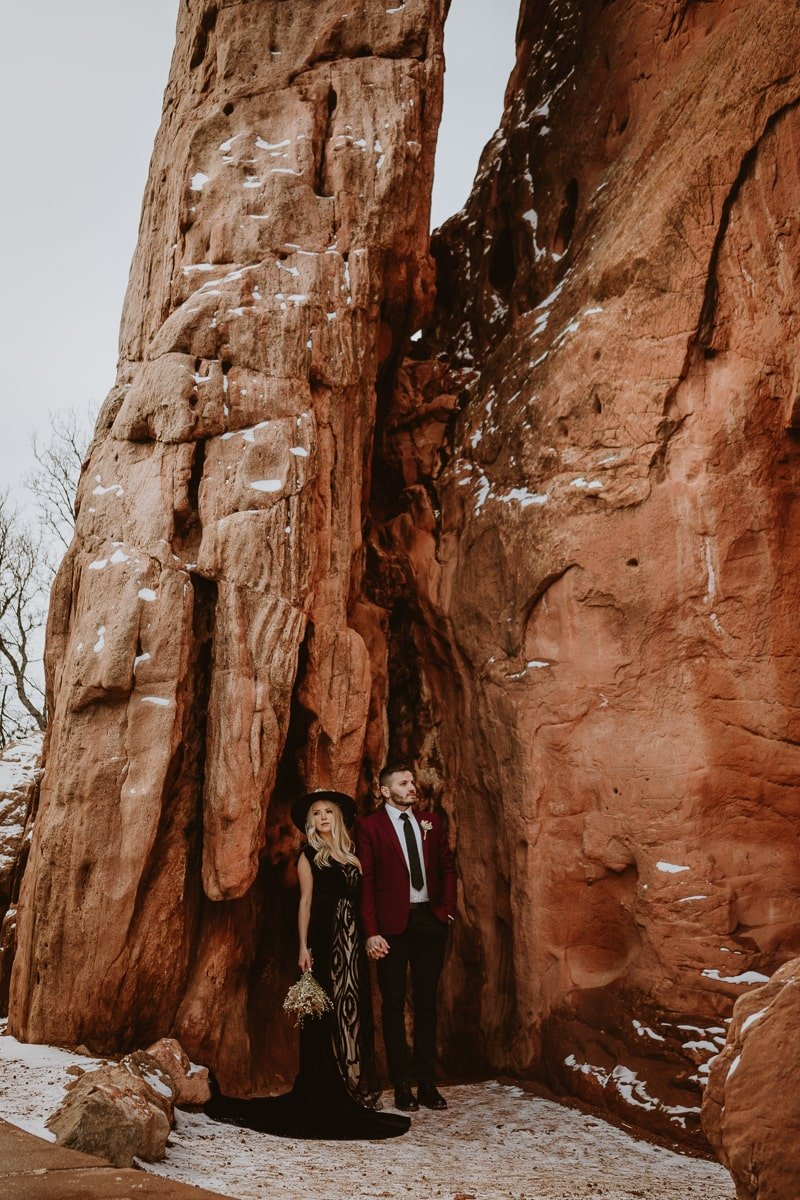 Couple poses in wedding attire after their elopement in the middle of Sentinel Plaza at Garden of the Gods