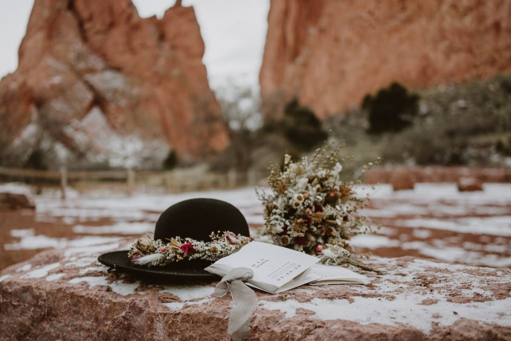 Winter elopement details at Garden of the Gods on a rock - vow books, hat, and dried floral bridal bouquet