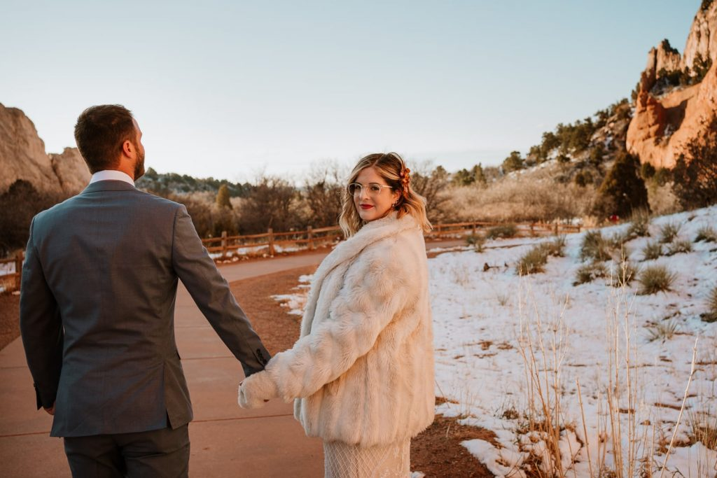 Bride looks back at camera as they hold hands and walk past Jaycee Plaza at this winter Garden of the Gods elopement