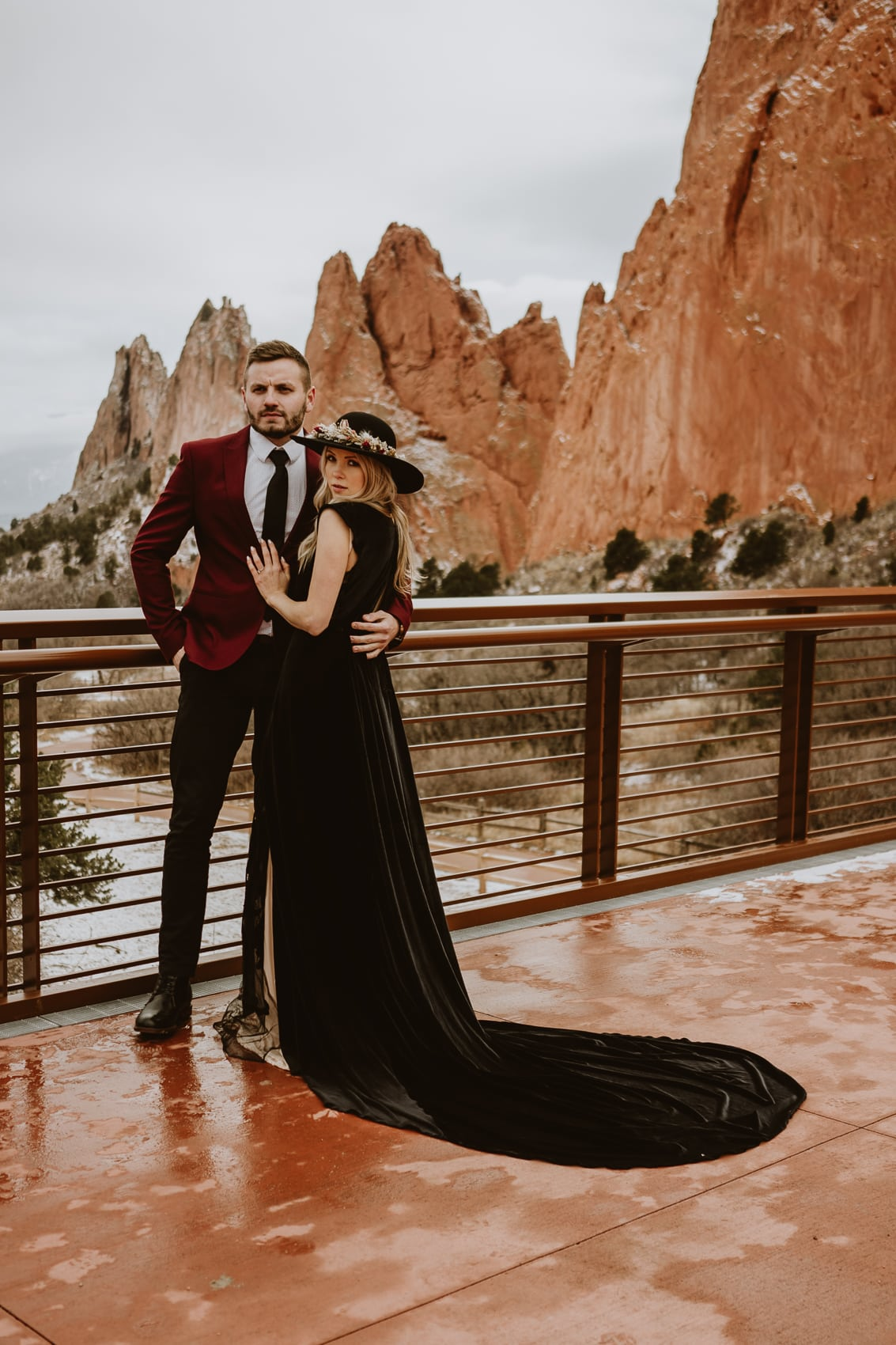 Bride and groom pose on a platform in front of the jagged rock formations for Garden of the Gods wedding photos