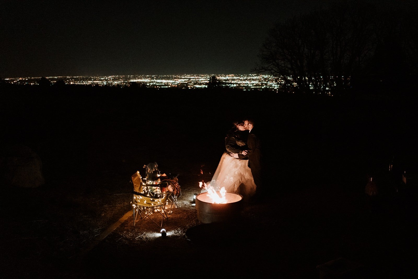 Bride and groom hold each other and kiss next to the campfire at Cheyenne Mountain State Park with the city lights of Colorado Springs lighting up behind them
