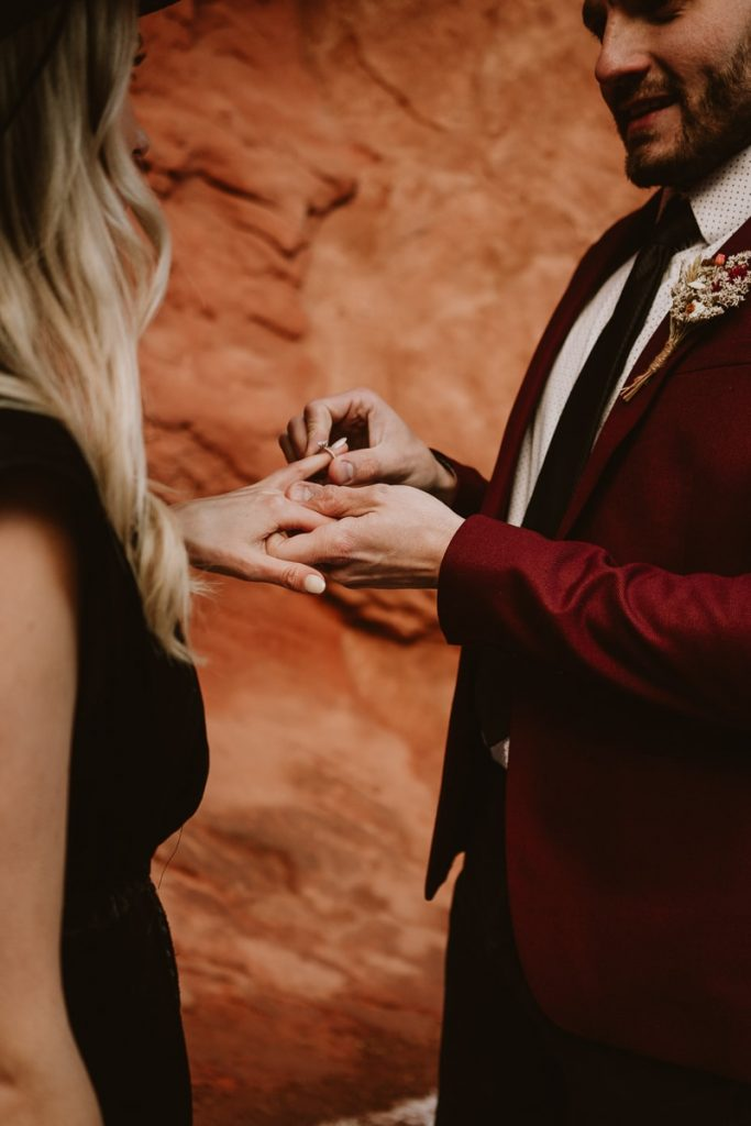 Groom puts wedding ring on his new brides finger