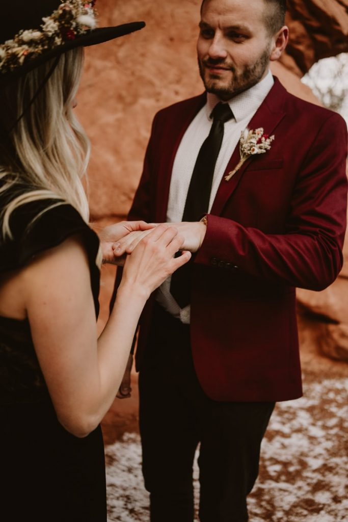 Bride puts on the groom's wedding ring as he looks into her eyes