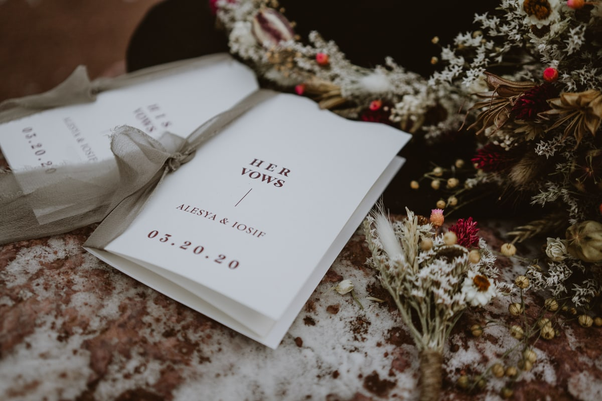 Closeup details of vow books from Luna Lynn Creative, elopement and wedding stationary for this moody Garden of the Gods elopement