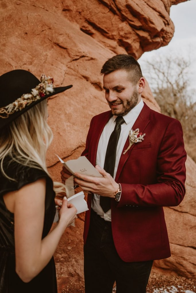 Groom laughs as he reads from his vow book to his bride during their colorful elopement at Garden of the Gods