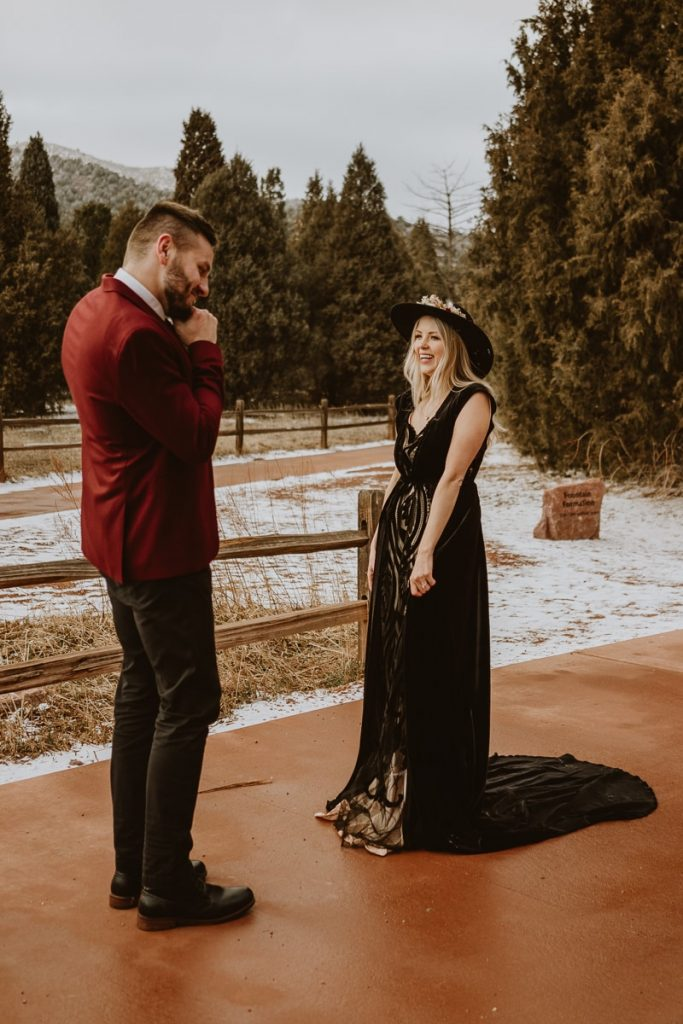 Groom and bride laugh together the very first time they see each other for the first look