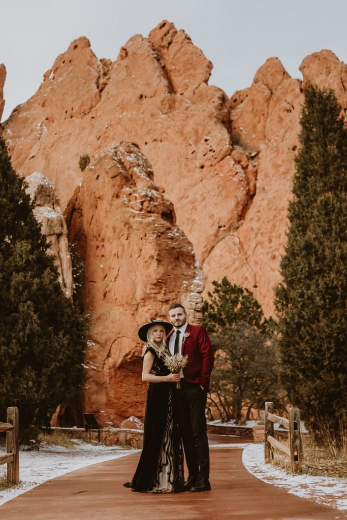 Bride and groom pose in front of the stunning rock formations for their Garden of the Gods elopement