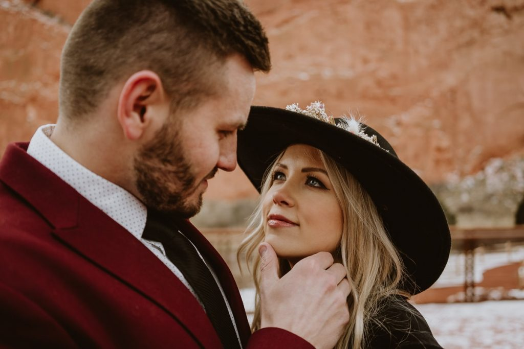 Groom grabs the chin of his bride and looks into her blue eyes at this romantic and moody Garden of the Gods elopement