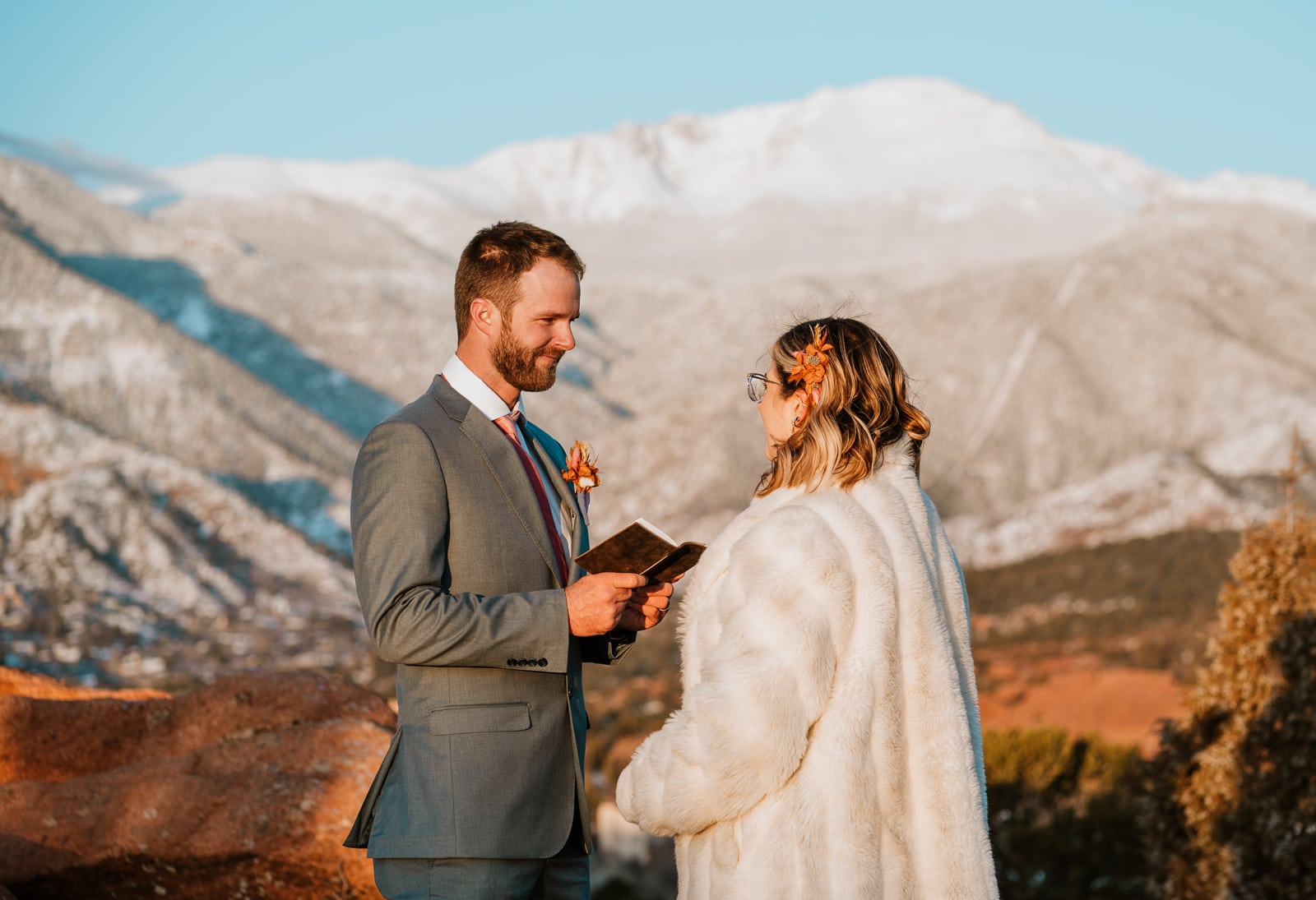 Groom reads his handwritten vows as Pikes Peak glows behind him during this romantic sunrise elopement in March at Garden of the Gods