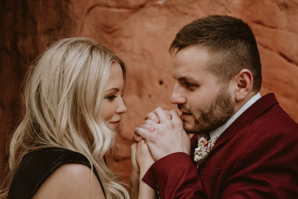 Groom tries to warm up his new bride's hand during their chilly winter elopement at Garden of the Gods