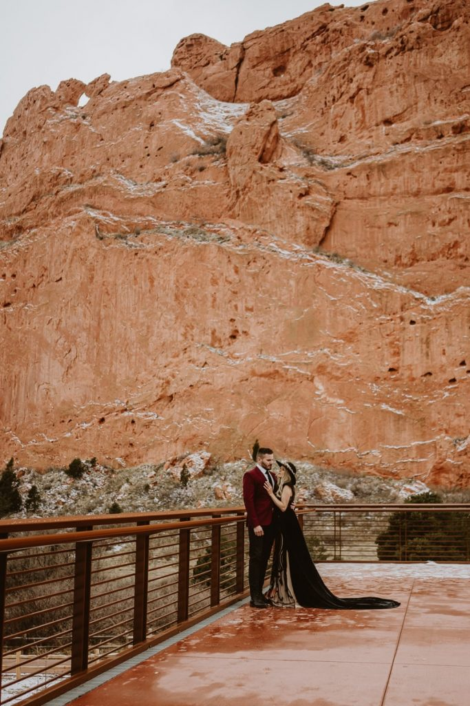 Bride and groom pose in front of the legendary kissing camels for this winter Garden of the Gods Colorado Springs elopement