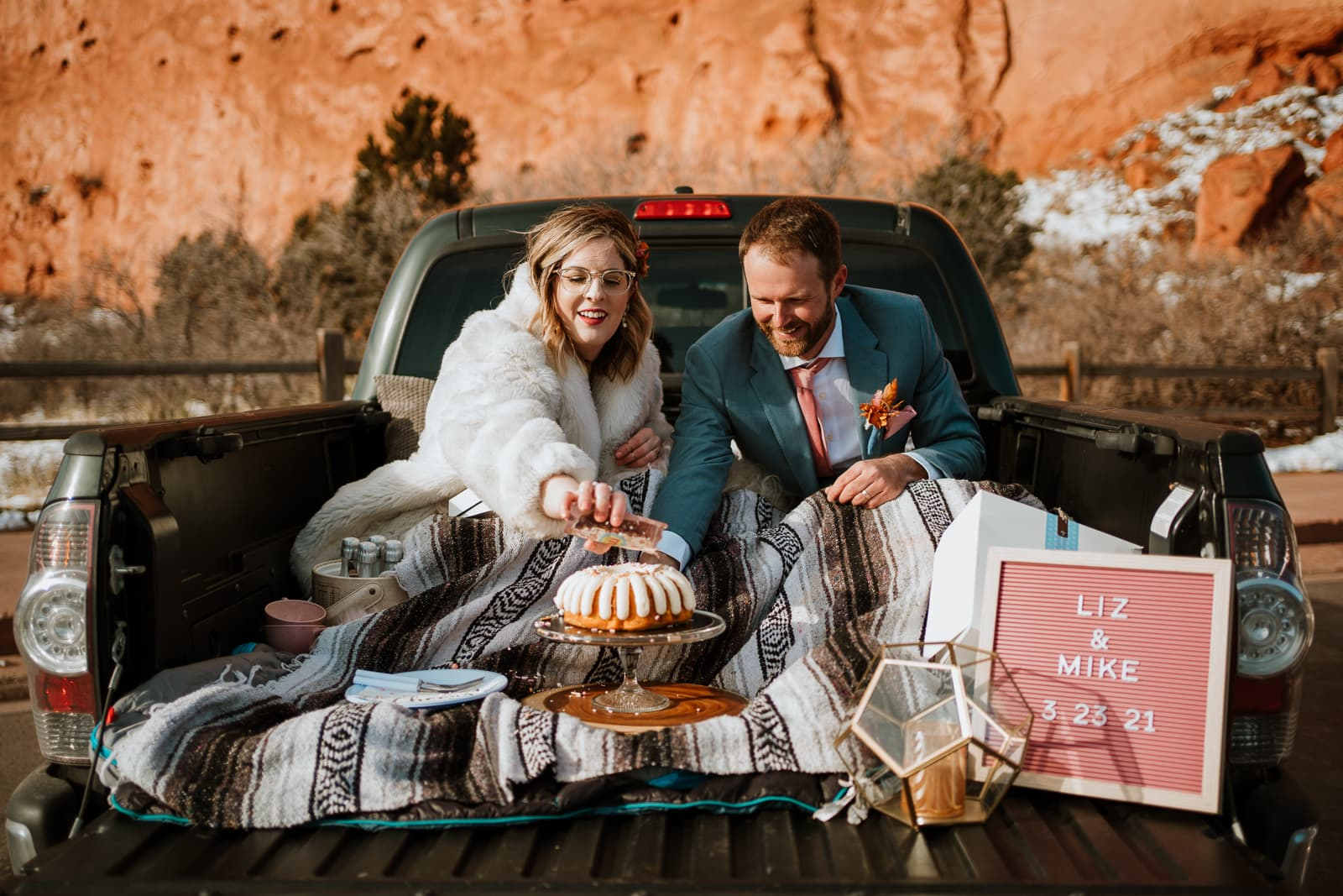 Bride and groom decorate their cake while enjoying their picnic in the back of their pickup truck at Garden of the Gods
