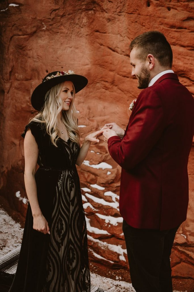 Groom puts wedding ring on his new bride's finger during their romantic Garden of the Gods wedding photos