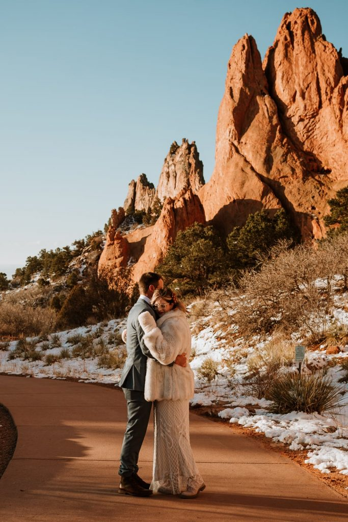 Bride and groom cuddle in the sunlight near Sentinel Plaza for their Garden of the Gods elopement