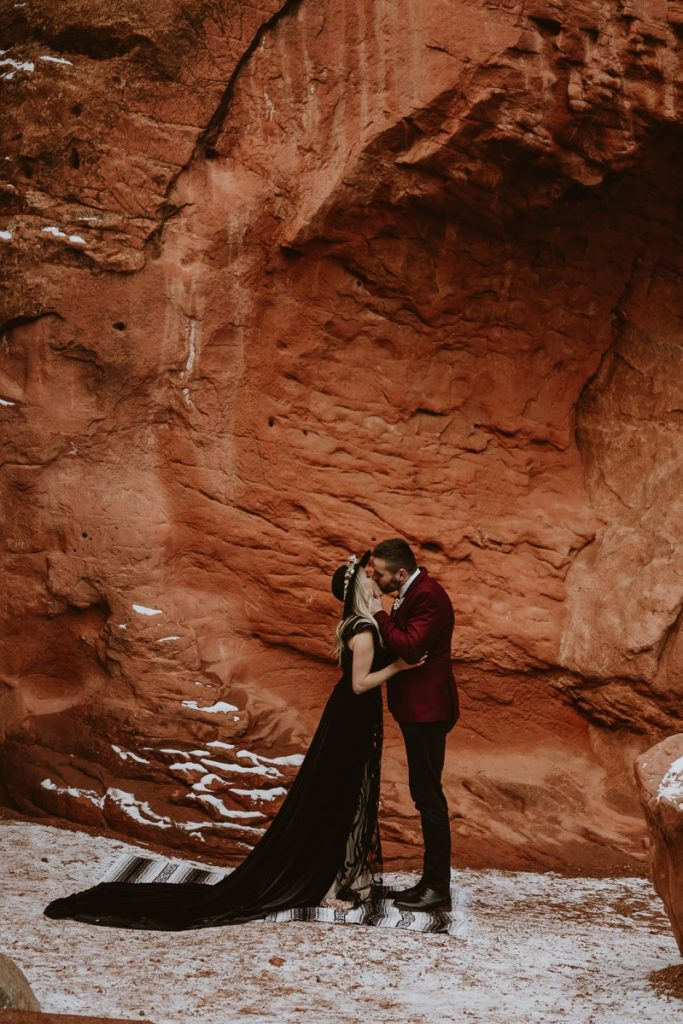 Groom grabs the bride's face and kisses her the moment they exchanged rings during this adventurous elopement at Garden of the Gods