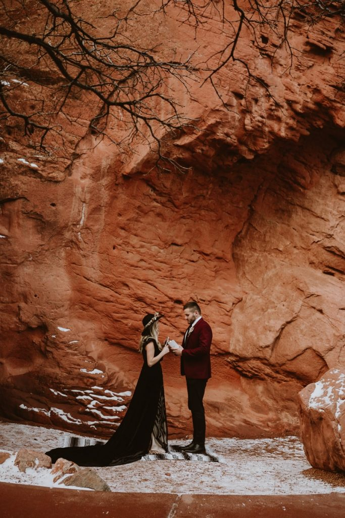 Wide photo of bride and groom reading their vows in Sentinel Plaza for their Garden of the Gods wedding photos