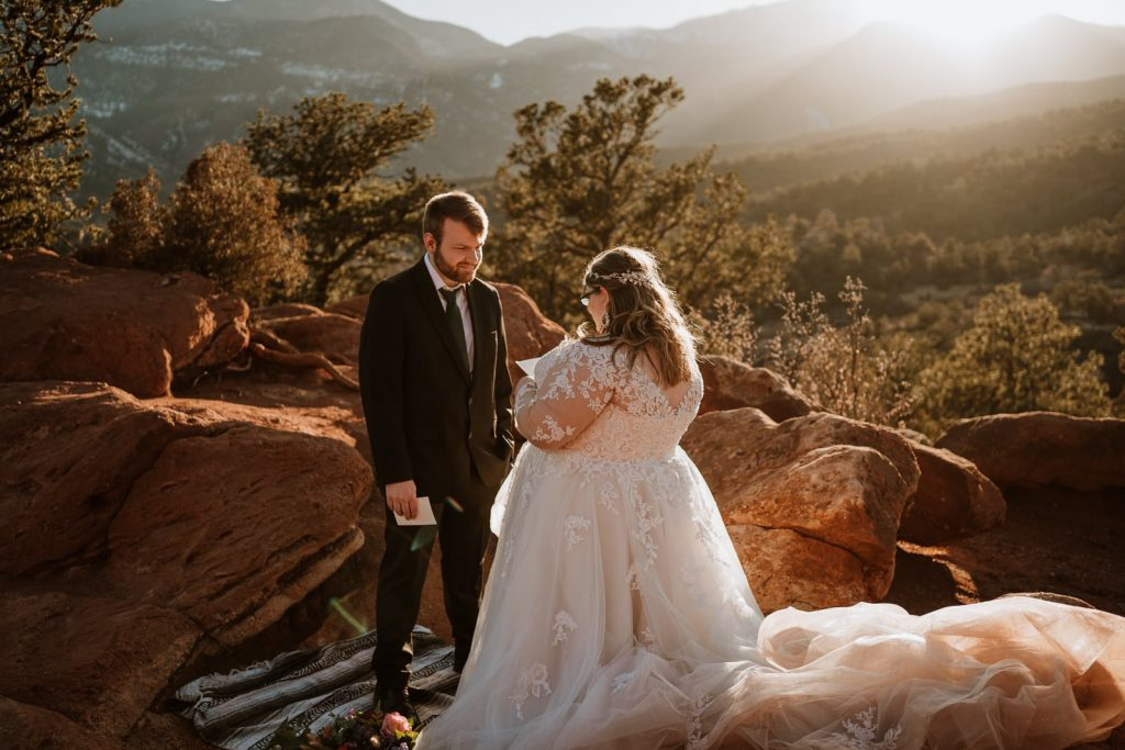 Bride and groom read their vows at sunset during their romantic elopement at Garden of the Gods