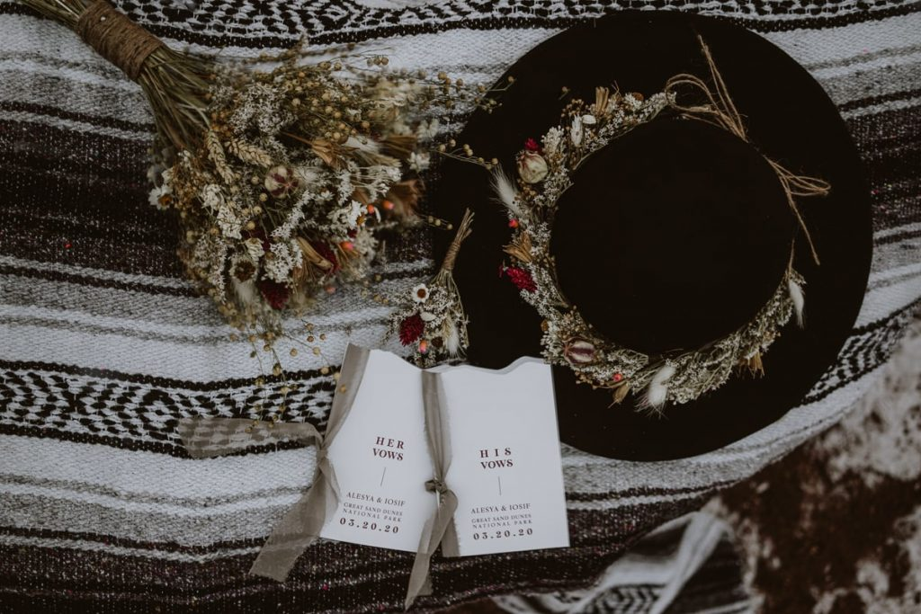 Closeup details of hat, dried floral bouquet, and vow books from Luna Lynn Creative, elopement and wedding stationary laid out on a black and white Mexican blanket