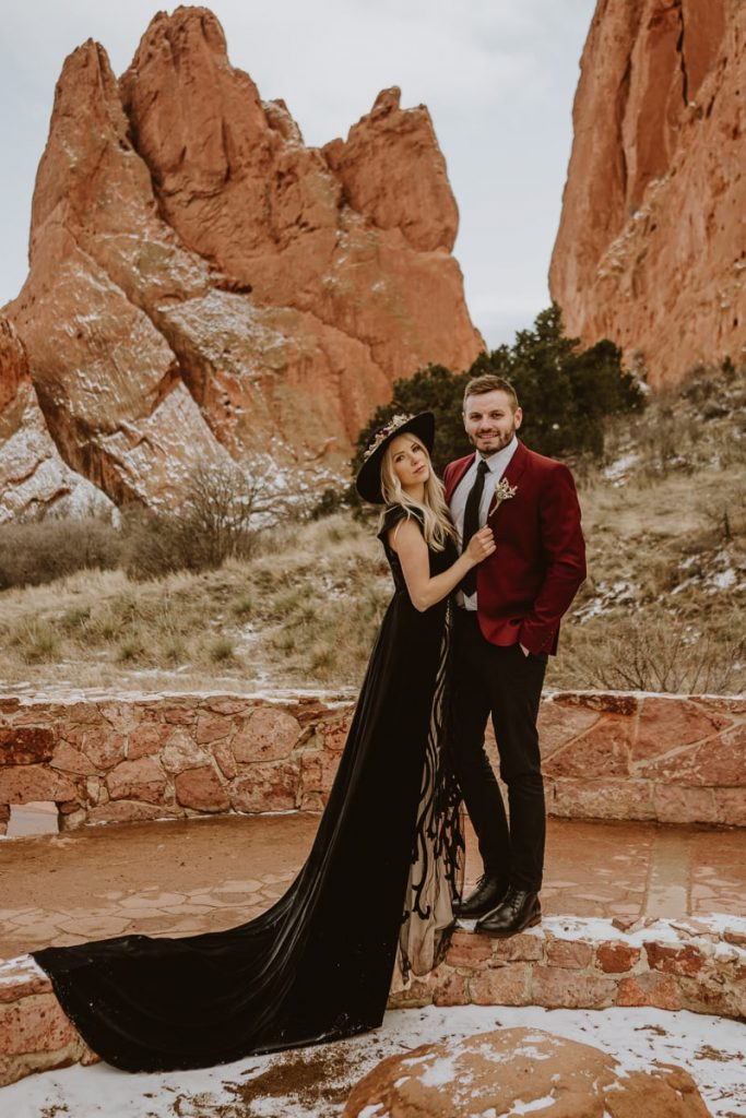 Bride and groom pose on the wall and look into the camera at Jaycee Plaza. This trail is a great place for Garden of the Gods elopement pictures.