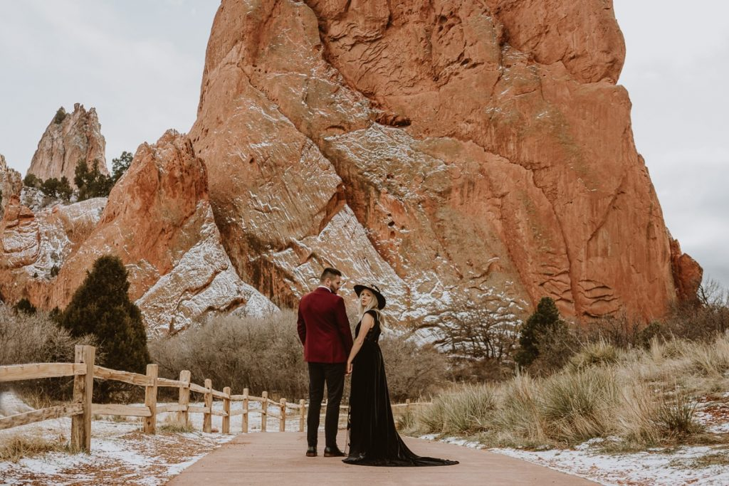 Groom looks at bride as they walk down Central trail for this Garden of the Gods elopement image