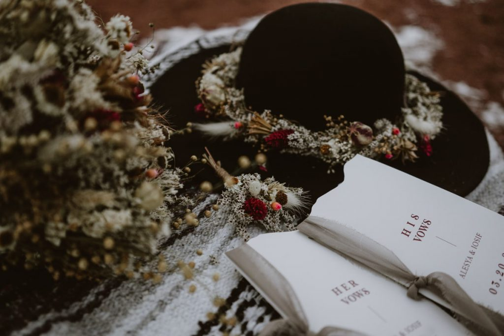 Closeup details of hat, dried floral bouquet, and vow books from Luna Lynn Creative, elopement and wedding stationary