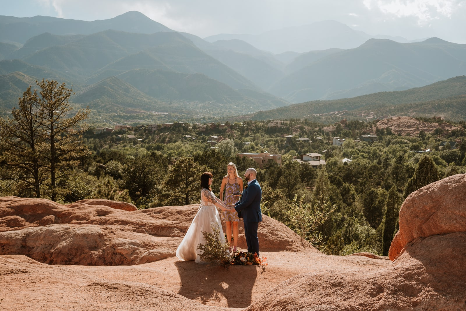 Couple holds hands and reads their vows before sunset at High Point Overlook for their Garden of the Gods fall intimate wedding