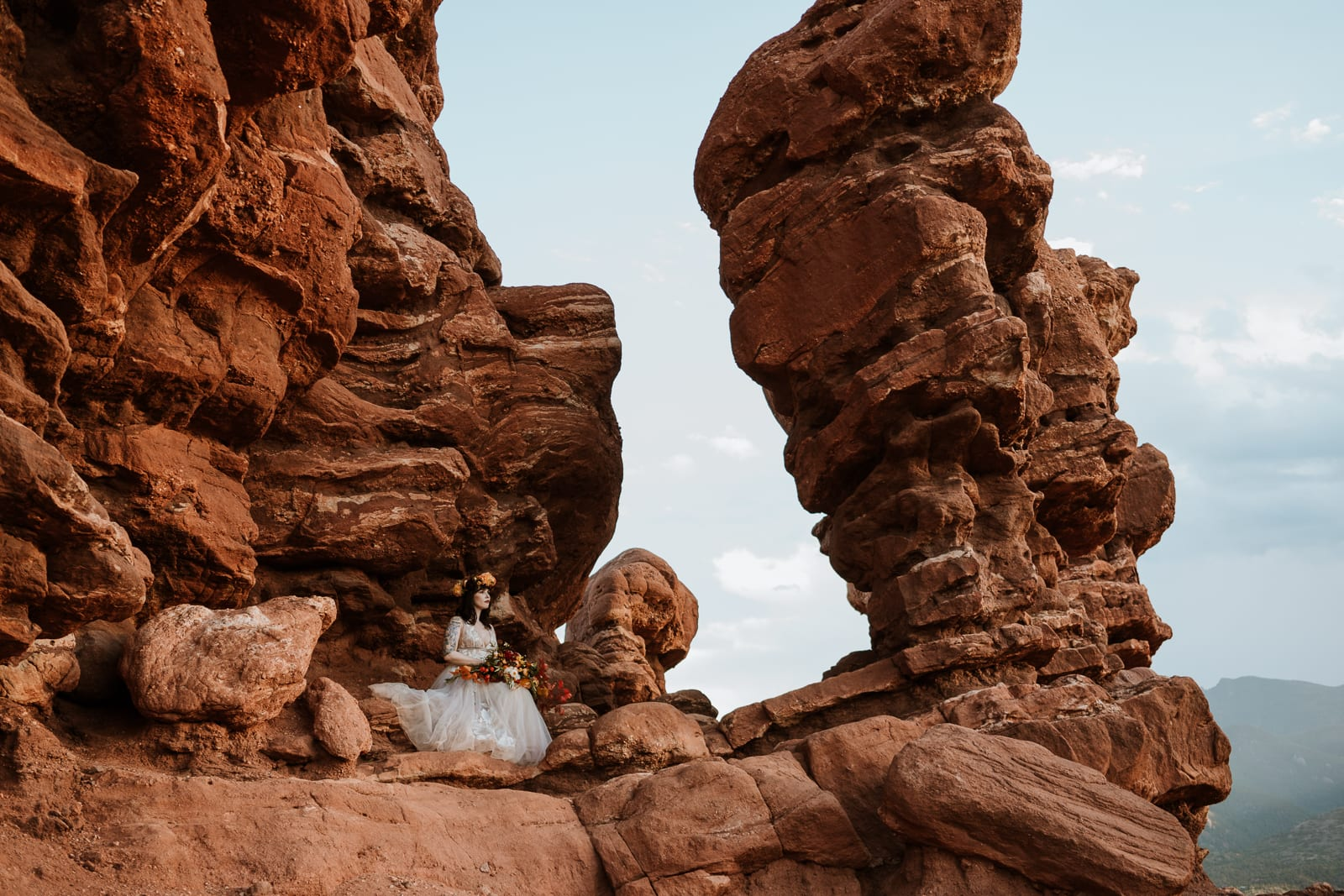 Bride sits next to a rock formation with her colored fall bouquet for her Garden of the Gods elopement