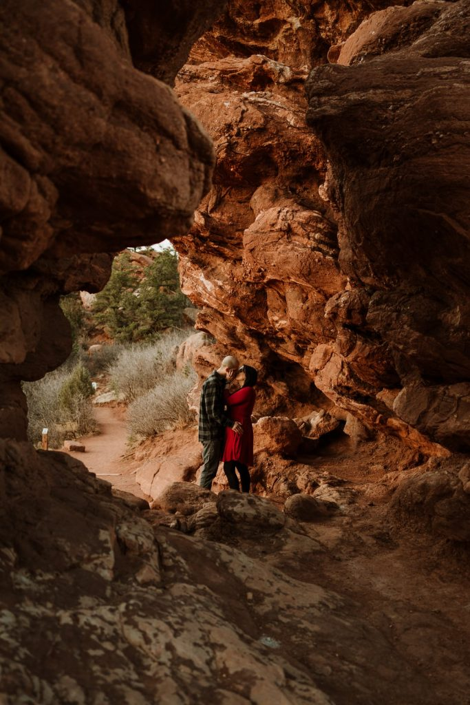 Couple kisses in the crevices of the rocks during the spring engagement session at Garden of the Gods Colorado Springs