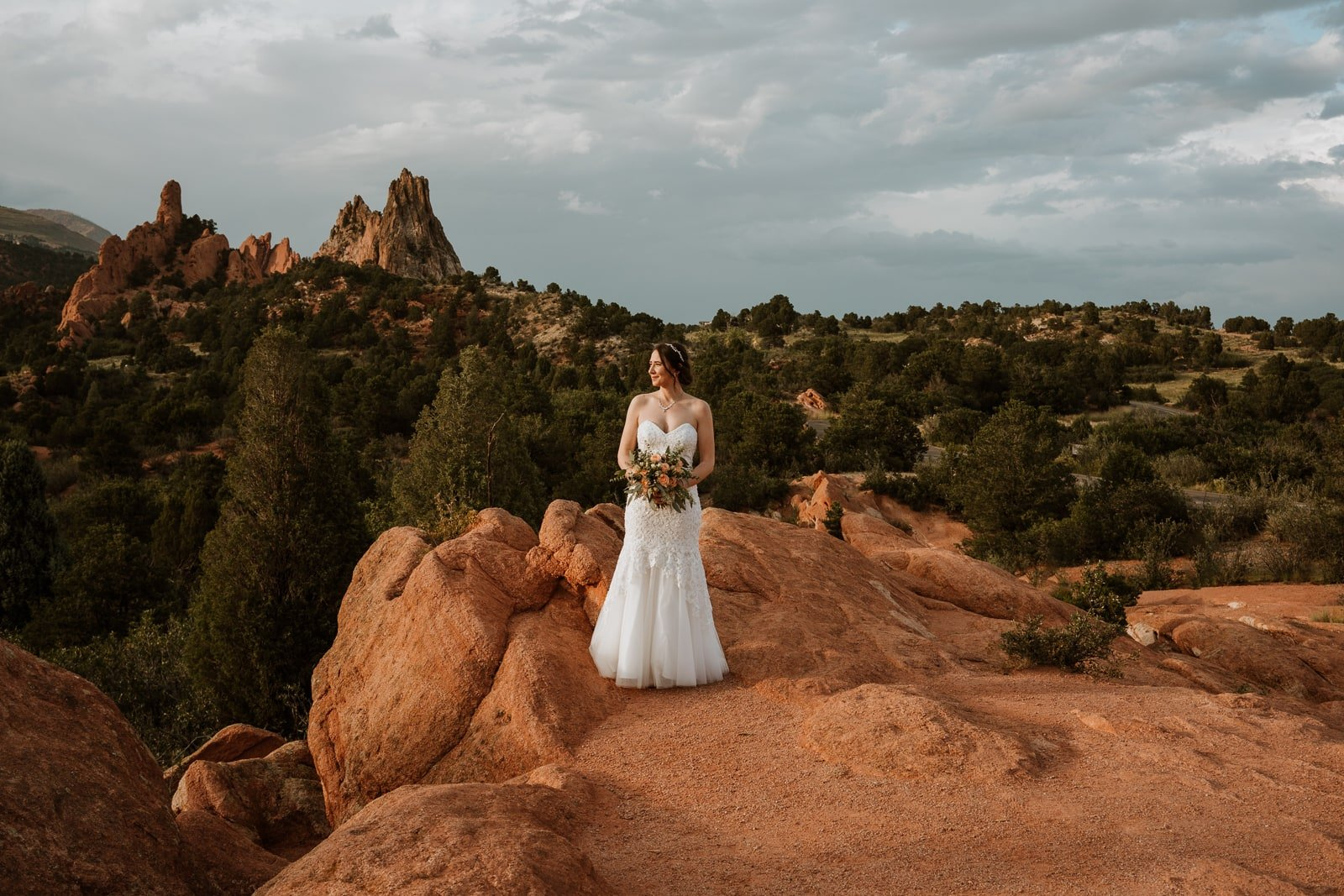 Bride stands on a rock and looks at the sunset with Central Garden glowing in the background for her summer Garden of the Gods elopement