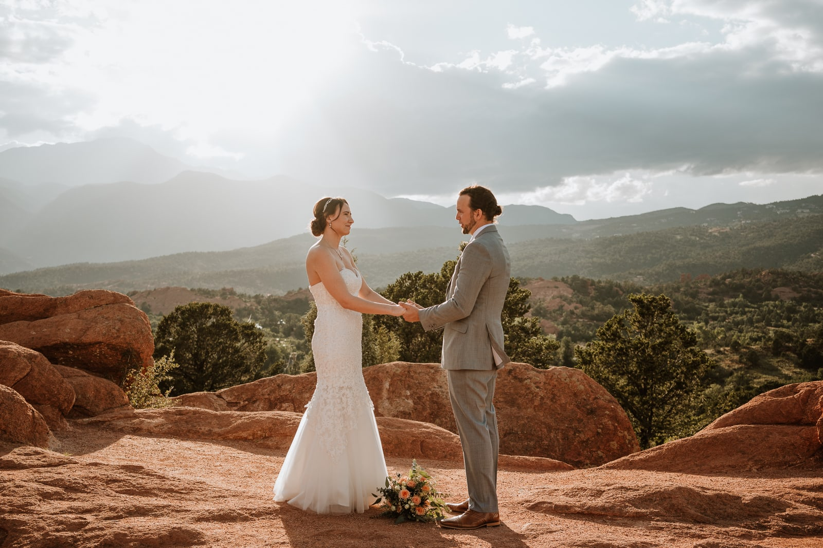 Bride and groom hold hands as they say their vows by heart at High Point Overlook in Garden of the Gods
