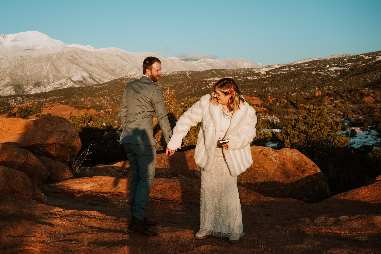 Bride and groom high five each other after getting married at sunrise at Garden of the Gods
