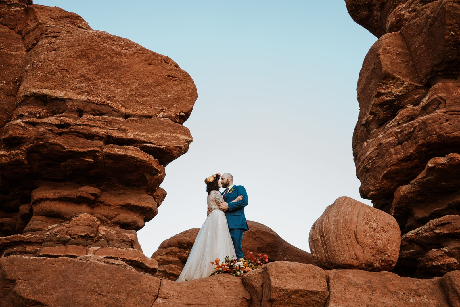 Bride and groom stand in cut out of unique rock formation at Garden of the Gods for their portraits