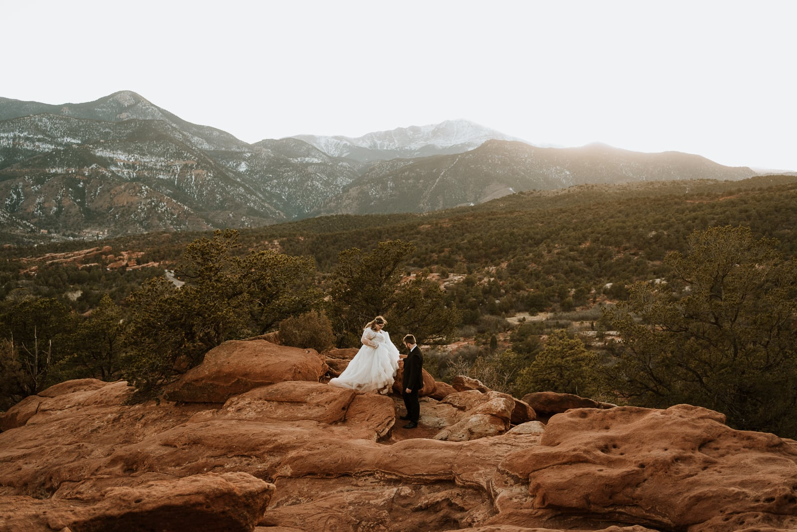 Groom holds his brides hand as she walks down the red rocks at Garden of the Gods for their intimate wedding ceremony