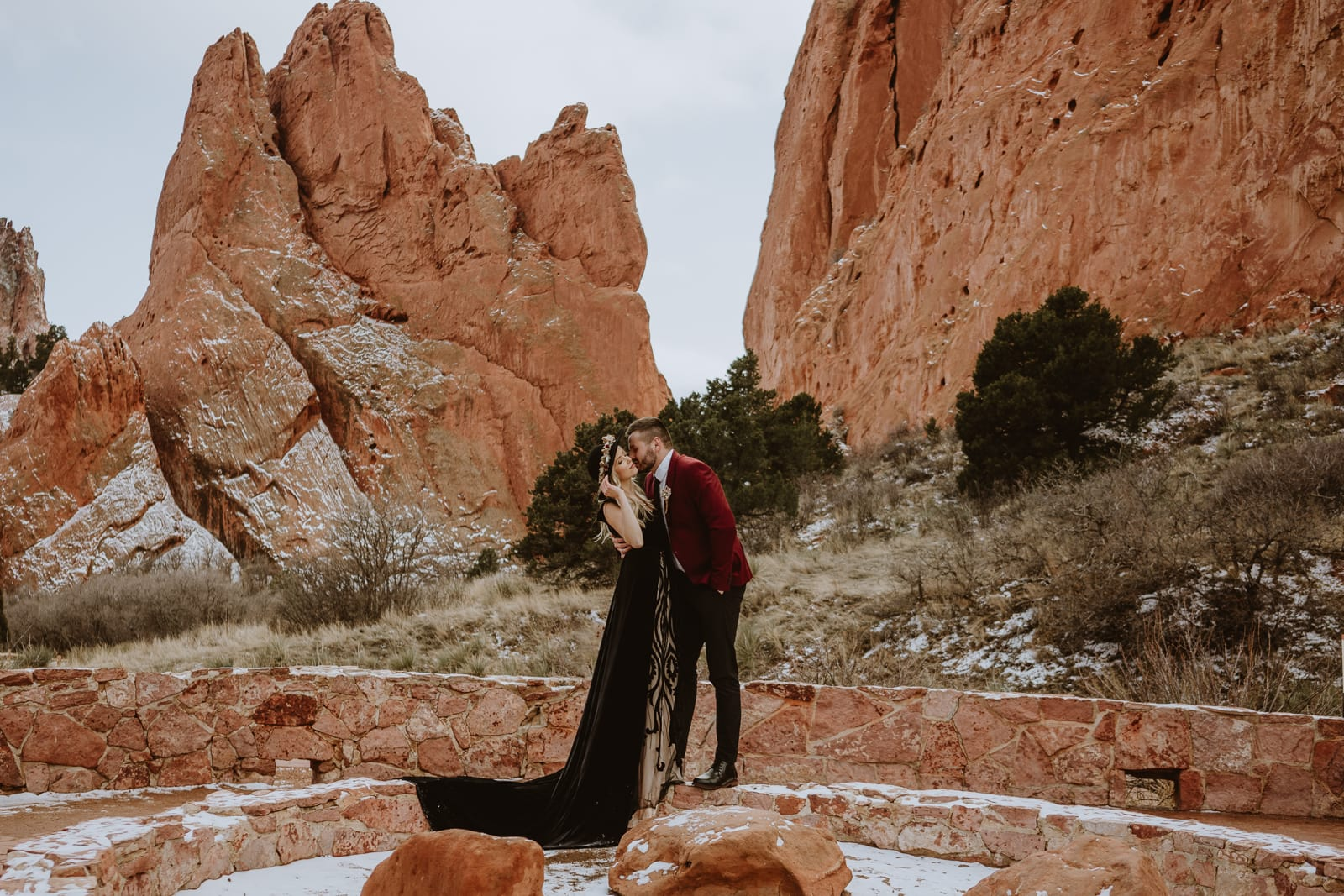 Bride and groom stand on the wall of Jaycee Plaza, a spot for an intimate wedding or elopement at Garden of the Gods