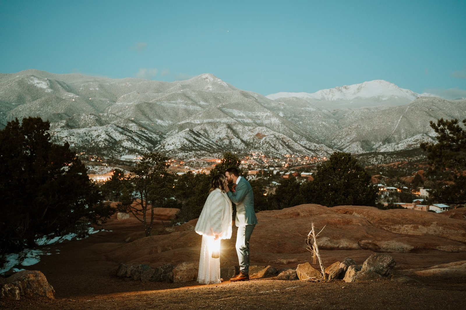 Bride and groom share a kiss just before sunrise for this winter Garden of the Gods elopement in March