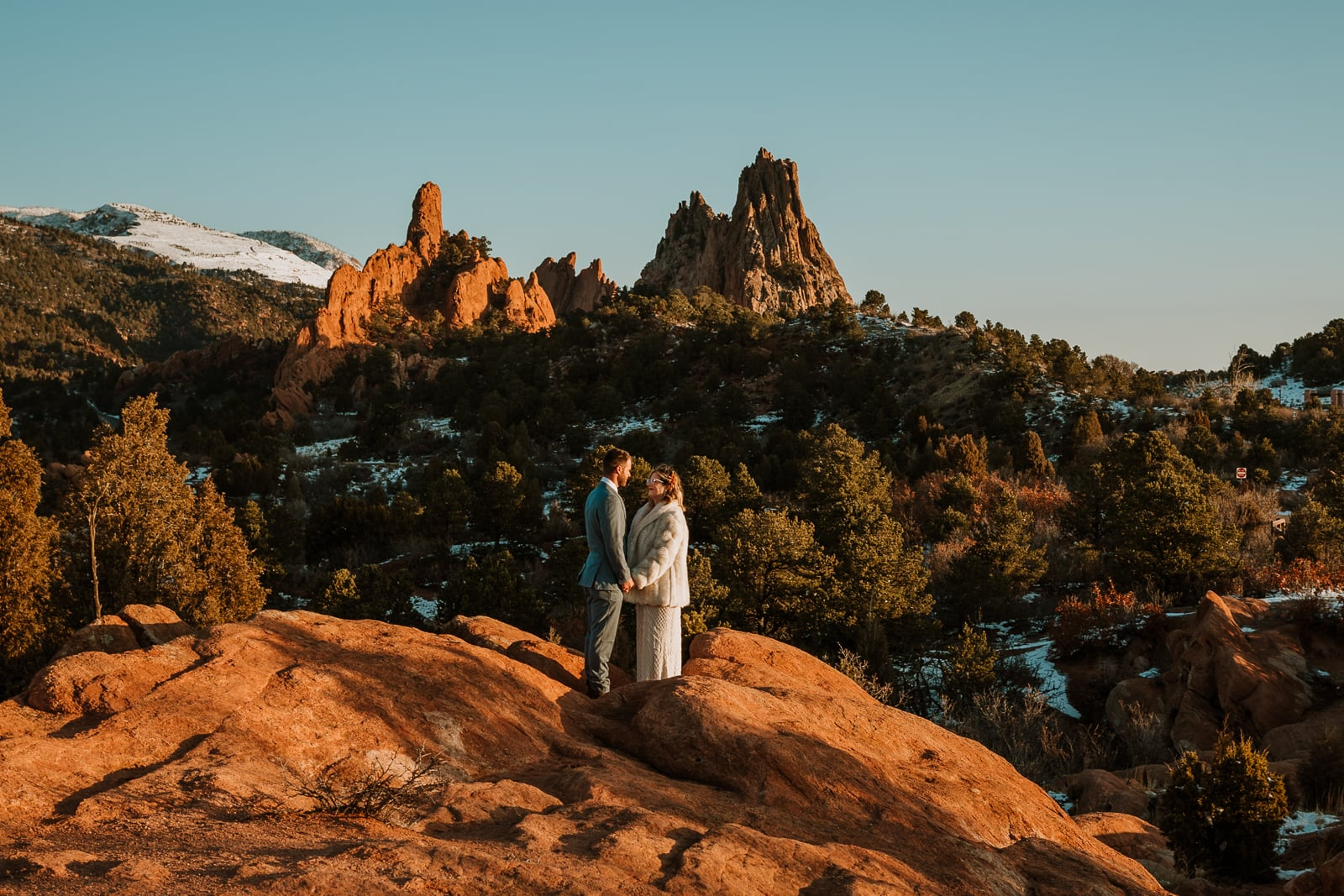 Wide photo of bride and groom standing on a rock at sunrise during their Garden of the Gods intimate winter wedding