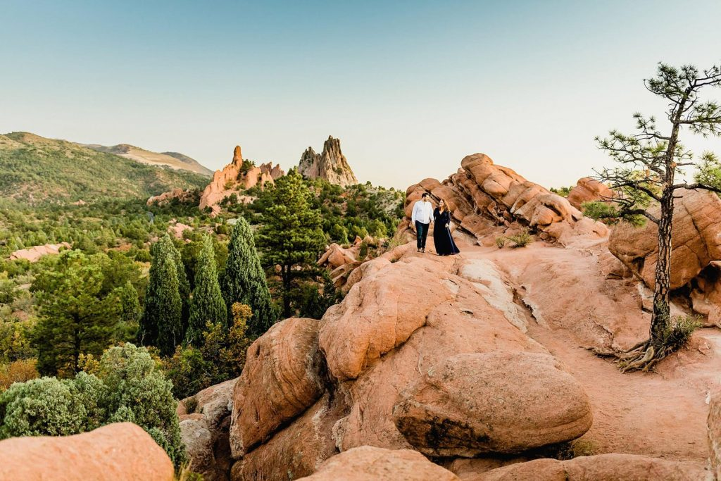 Couple walks together among the red rocks of Garden of the Gods, photo by Lauren Casino Photography