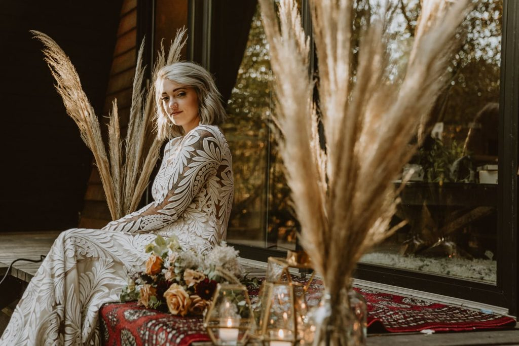 Bohemian bride sits in the sun on the patio of the AirBNB she rented for her elopement ceremony. The sunset is perfectly lighting up her face and the decor sitting beside her.