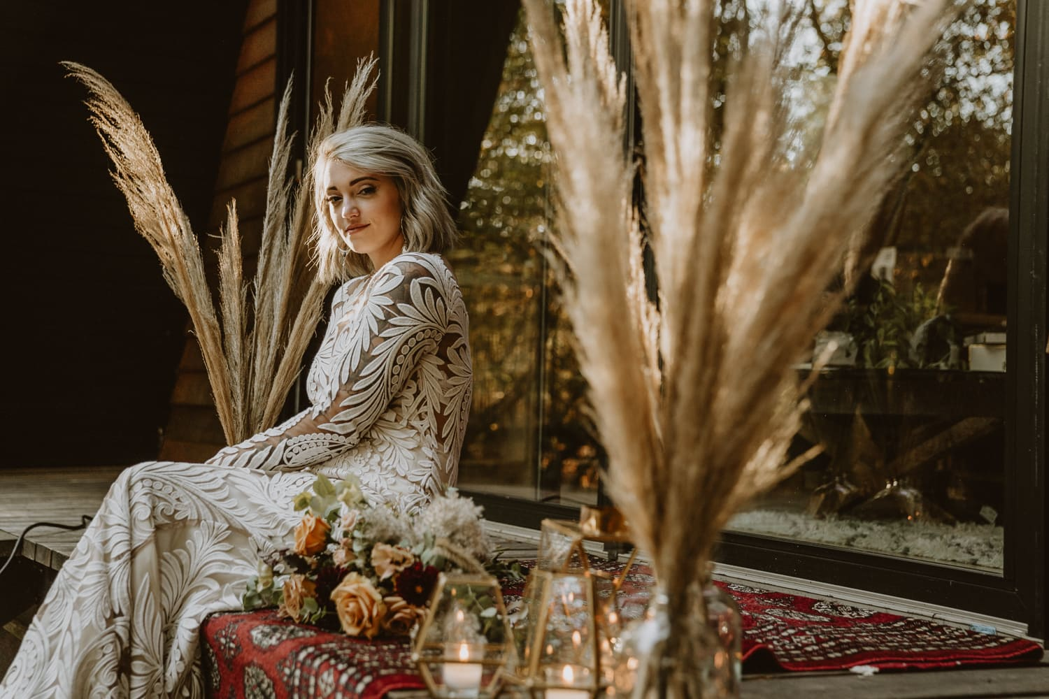 Bride poses next to her elopement decor. Bohemian decor with pampas grass and candles was high on her elopement checklist
